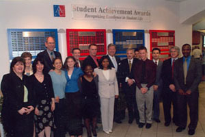 Students and faculty stand next to the student achievement award plaques.